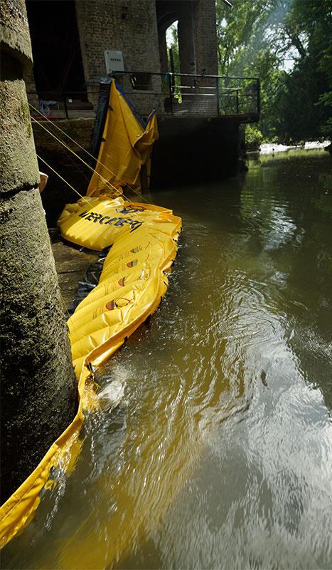 """"""" Ataguía Flexible Water-Gate © WA-2850 en L. Apoyado en un muro del molino en la margen izquierda y sobre un pilote de un puente aventador en medio del río."""""""