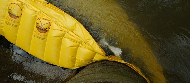 Soporte de un extremo de una ataguía flexible Water-Gate © contra un pilar de puente. La ataguía sigue la forma del soporte.